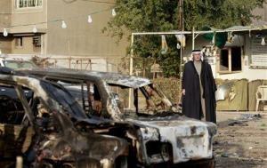 A man inspects the aftermath of a car bomb in Hurriya neighborhood, Baghdad, Iraq, Tuesday, Dec. 18, 2012.
