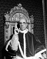 In this file photo dated Sept. 1945, Pope Pius XII, wearing the ring of St. Peter, raises his right hand in a papal blessing at the Vatican. .