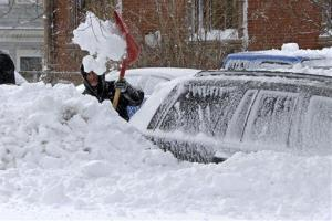 A man shovels snow off his car on M street in the South Boston neighborhood of Boston Saturday, Feb. 9, 2013 in Boston.