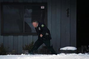 A US Forest Service Law Enforcement officer searches a home for Christopher Dorner in Big Bear Lake, Calif, Saturday, Feb. 9, 2013.