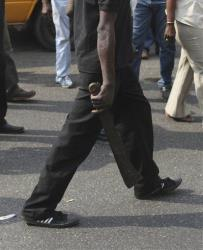 An unidentified member of Oodua People's Congress militia walks with a machete on a major street, during a protest against Boko Haram in Lagos, Nigeria, Thursday, Dec. 8, 2011.