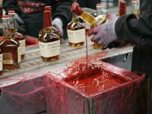 In this Wednesday, April 8, 2009, photo, a bottle of Maker's Mark bourbon is dipped in red wax during a tour of the distillery in Loretto, Ky.
