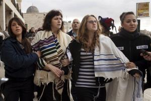 Wrapped in Jewish prayer shawls, Rabbi Susan Silverman, second left, along with her daughter Hallel Abramowitz, second right, are detained by police officers in Jerusalem's Old City, Feb. 11, 2013.