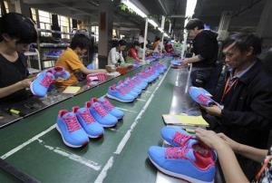 Chinese workers manufacture sports shoes at a shoe factory in Jinjiang in southeast China's Fujian province Friday Nov. 9, 2012.
