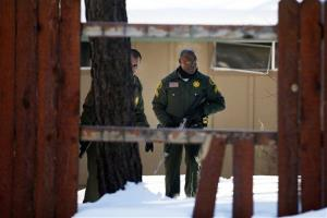 San Bernardino County Sheriff's officers Bernabe Ortiz, left, and Ken Owens search a home for former Los Angeles police officer Christopher Dorner in Big Bear Lake, Calif, Sunday, Feb. 10, 2013. The hunt for the former Los Angeles police officer suspected in three killings entered a fourth day in snow-covered...
