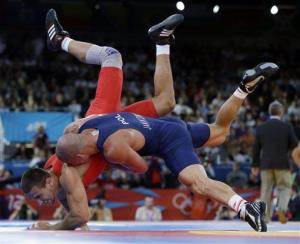 In this Monday, Aug. 6, 2012 photo, Amer Hrustanovic of Austria competes against Damian Janikowski of Poland, in blue, during the 84-kg Greco-Roman wrestling competition at the 2012 Summer Olympics.