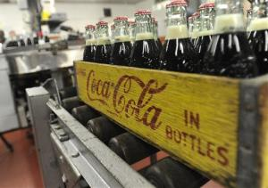 In this Tuesday, Oct. 9, 2012, photo, bottles in the last run are prepared for crates at the Coca-Cola Bottling Company in Winona, Minn.