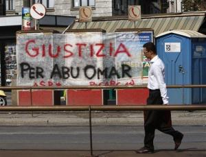 A man walks past a banner with writing reading Justice for Abu Omar, in front of Milan's court house Wednesday, Sept. 23, 2009.