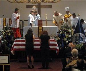 Two women bow before the casket of slain ICE Special Agent Jaime Zapata during a funeral mass at the Brownsville Special Events Center in Texas, Feb. 22, 2011.