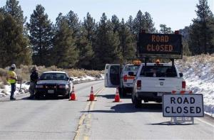 A law enforcement officer stands by a roadblock at Route 38 near Big Bear, Calif., on Wednesday.