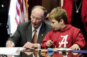 Gov. Robert Bentley, left, draws with 6-year-old Ethan Gilman during a visit to the Governor's Office in Montgomery, Ala. on Wednesday, Feb. 13, 2012.