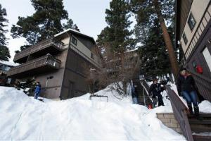 Members of the news media are shown outside a home, at left, in Big Bear, Calif., where the owners of the cabin were taken hostage by fugitive Christopher Dorner.