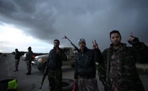 Libyan military soldiers wave victory signs while standing on alert on the side of the highway to Benghazi downtown, in Benghazi, Libya, Friday, Feb. 15, 2013.