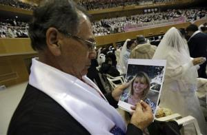 Newly-married groom Juan Proano from Miami holds a wedding ring and a picture of his bride, who didn't appear, during a mass wedding ceremony in Gapyeong, South Korea, Sunday, Feb. 17, 2013.