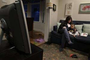 A study participant, left, looks on as her son Joe, 2, is given a special treat of a little TV time Tuesday, Feb. 12, 2013 at their home in Seattle.