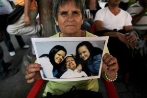 Carmen Rondon poses with a photo of Venezuela's President Hugo Chavez with his daughters, in Bolivar square where a vendor is selling the pictures in Caracas, Venezuela, Friday, Feb. 15, 2013.