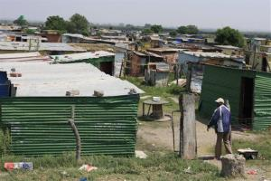A striking miner shouts at a friend at his home in an informal settlement near a mine near Rustenburg, South Africa, on Wednesday, Nov. 14, 2012.