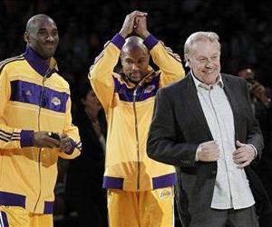 Jerry Buss walks out onto the court during the NBA championship ring ceremony as Kobe Bryant and Derek Fisher look on, Oct. 26, 2010.