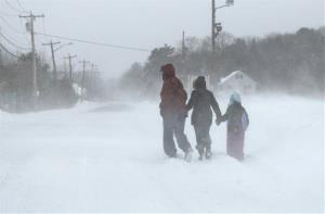 Pedestrians make their way down a road during whiteout conditions in Salisbury, Mass. Saturday, Feb. 9, 2013.