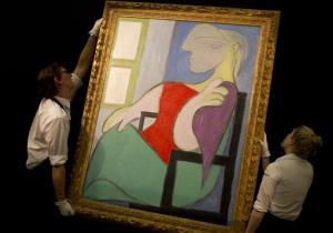 Two Sotheby's employees adjust a painting by Pablo Picasso entitled Femme assise pres d'une fenetre at Sotheby's auction house during a press preview in London, Thursday, Jan. 31, 2013.