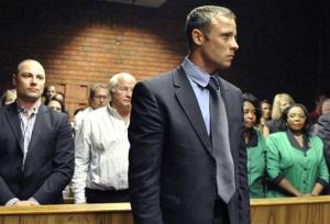 Oscar Pistorius stands following his bail hearing, as his brother Carl, left, and father Henke, second left, look on in Pretoria, South Africa, Tuesday, Feb. 19, 2013.