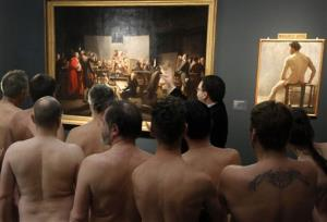 Naked museum visitors look at images in the exhibit Nude Men from 1800 to Today during a special opening to friends of nudism at the Leopold Museum, Vienna, Austria.