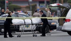 The Orange County coroner's office wheels a body to a waiting van in Orange, Calif.