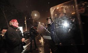 A wounded protester speaks to riot policemen during a protest against high electricity prices in Sofia last night.