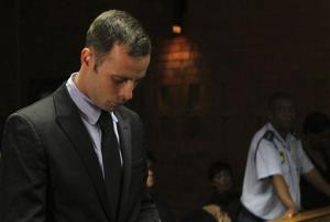 Olympic athlete Oscar Pistorius stands inside the court as a police officer looks on during his bail hearing  in Pretoria today.