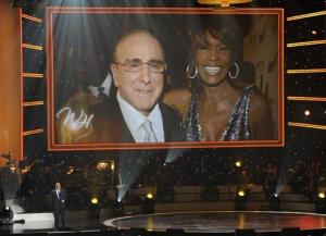 Clive Davis speaks onstage underneath a photo of himself with singer Whitney Houston at We Will Always Love You: A Grammy Salute to Whitney Houston, on Thursday, Oct. 11, 2012, in Los Angeles.