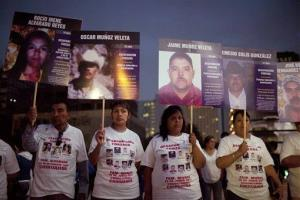 FILE - In this May 9, 2012 file photo, people hold photographs of their relatives who went missing during a protest that is part of the campaign March of National Dignity. Mothers searching their sons and justice held at the Revolution Monument in Mexico City.  A new report by a...