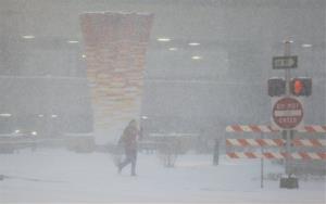 A pedestrian walks along the sidewalk in Kansas City, Mo., Thursday.