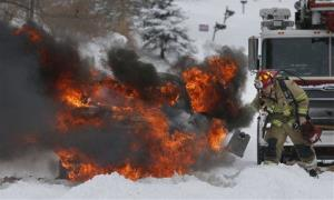 A Lawrence firefighter places wheel blocks as he prepares to extinguish a vehicle fire in Lawrence, Kan., Thursday.