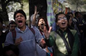 Protesters shout slogans near Indian parliament to protest a new sexual violence law as the parliament convenes in New Delhi yesterday. They say the law is inadequate.