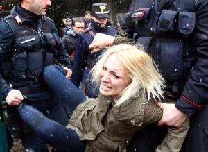 Police take away a woman protesting where Silvio Berlusconi was voting, in Milan, Italy, Sunday, Feb. 24, 2013.