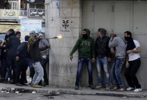 Palestinians take cover during clashes with Israeli troops in  the West Bank city of Hebron yesterday.