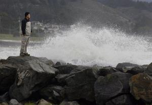 A man stands on a sea wall at Pillar Point Harbor as a large wave crashes against it on Saturday, Jan. 26, 2008 in Half Moon Bay, California.