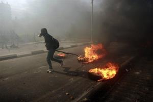 A man burns tires during a protest to support Palestinian prisoners  outside Ofer, an Israeli military prison near the West Bank city of Ramallah.