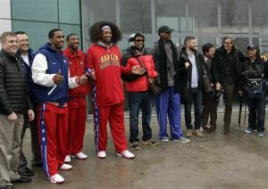 Dennis Rodman, fifth from right, poses with three members of the Harlem Globetrotters, in red jerseys, and a production crew for the media upon arrival at Pyongyang Airport, North Korea, Feb. 26, 2013.