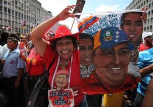 A supporter of Venezuela's President Hugo Chavez on Wednesday holding a painting of the ailing leader during an event to commemorate the violent street protests of 1989 known as the Caracazo.