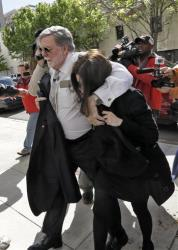 Casey Anthony is protected from the media by her attorney Cheney Mason as she arrives at the United States Courthouse for a bankruptcy hearing Monday, March 4, 2013.