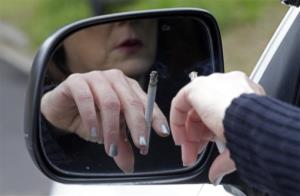 In this Saturday, March 2, 2013 photo, a woman smokes a cigarette while sitting in her truck in Hayneville, Ala.