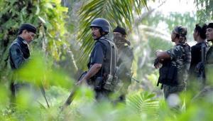 A group of Malaysian police commandos stand guard near where Filipino gunmen earlier ambushed and killed five Malaysian policemen.