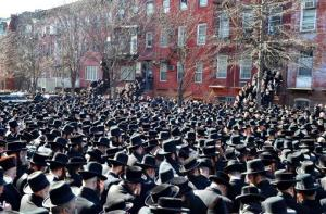 Orthodox Jewish mourners gather outside the a synagogue in Brooklyn's Williamsburg neighborhood for the funeral of Nachman and Raizy Glauber.