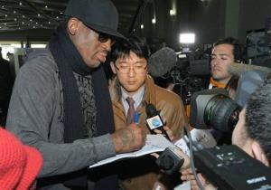 Former NBA star Dennis Rodman signs his autograph for a fan at the Pyongyang Airport.