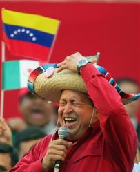 In this 2005 file photo, Venezuela's Hugo Chavez wears a Mexican sombrero as he sings a Mexican ranchera song at a rally in Caracas, Venezuela.
