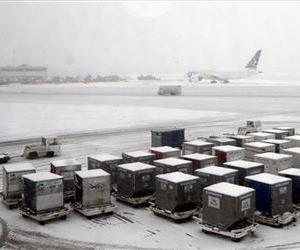 Snow covers containers at O'Hare International Airport in Chicago, Tuesday, March 5, 2013.