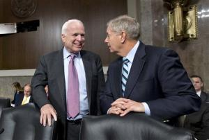 In this Feb. 14, 2013, photo, John McCain talks with Lindsey Graham on Capitol Hill.