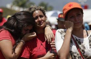 Women cry as they watch the funeral on a giant screen.