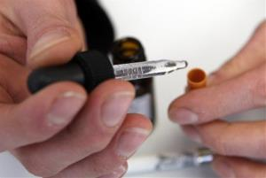 An e-cig user adds the liquid nicotine solution to the filter end of an electronic cigarette.